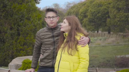 Teenage Caucasian boy hugging his lovely mother in the autumn park. Young redhead Caucasian woman posing with her son wearing eyeglasses outdoors. Family looking at each other, at camera, and smiling