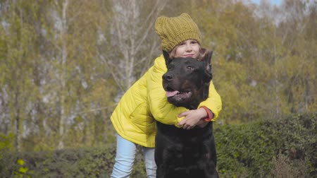 Smiling Caucasian girl in mustard hat and yellow coat hugging dog in the autumn park. Child spending weekends with her best friend outdoors. Kid and pet outdoors Stock Footage
