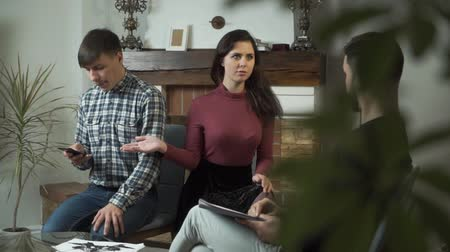 Portrait of cute Caucasian woman showing her spouse having internet addiction. Young girl complaining psychologist about permanent problems in relations. Wife or girlfriend trying to save husband Stock Footage