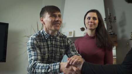 Close-up of satisfied Caucasian client shaking psychologists hand. His happy beautiful wife or girlfriend sitting next to him and smiling. Successful couples therapy
