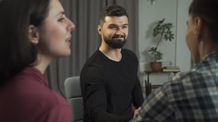 Portrait of bearded Caucasian man with black hair shaking hand of his patient. Handsome male psychologist and his satisfied clients after successful couples therapy. Professional psychoanalist Stock Footage