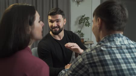 Young happy Caucasian family shaking psychologists hand and smiling. Successful end of the couples therapy. Psychoanalysis, satisfied clients, professional help