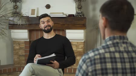 oposto : Portrait of nice Caucasian man sitting with papers, talking, smiling. Professional male psychologist telling story to patient sitting opposite. Individual therapy. Camera moving from left to right Stock Footage
