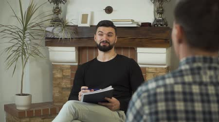 Adult Caucasian man sitting with papers, talking, and smiling. Professional male psychologist telling story to patient sitting opposite. Individual therapy. Camera moving from right to left