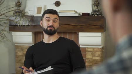 oposto : Close-up face of an adult Caucasian man sitting with papers, talking, and smiling. Professional male psychologist telling story to patient sitting opposite. Camera moving from right to left Stock Footage