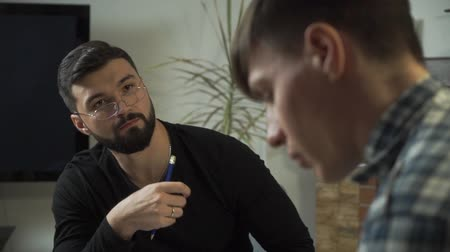Close-up of male Caucasian psychologist in eyeglasses listening to his patient. Young man came to the psychological office for the first time. Individual therapy, solving problems Stock Footage