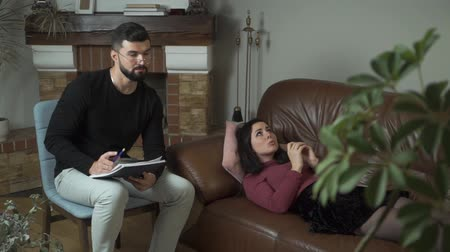 Young pretty Caucasian woman lying at the couch and talking to the male psychologist. Professional psychoanalist analysing his patients problems and taking notes. Individual therapy Stock Footage