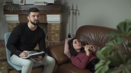 Young handsome Caucasian psychologist talking to his female client lying at the sofa. Sad woman listening to the professional carefully. Doctor analysing his patients problems. Individual therapy
