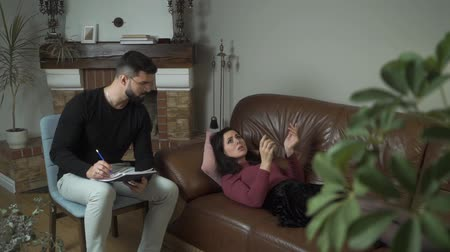 Downhearted young Caucasian girl gesturing emotionally and talking as lying at the couch. Male professional psychologist taking notes and shaking his head. Individual therapy Stock Footage