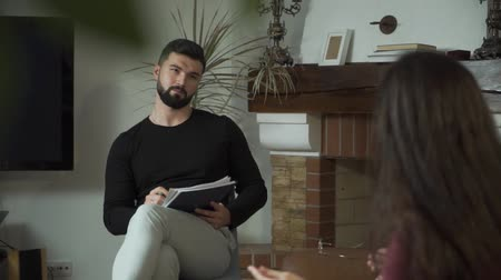Shooting over shoulder of young Caucasian woman gesturing emotionally and telling psychologist about her fears and problems. Desperate girl searching for professional help. Individual therapy