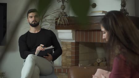 Portrait of a concentrated Caucasian male psychologist listening to his nervous patient. Shooting over shoulder of young woman gesturing emotionally and telling about her problems. Individual therapy Stock Footage