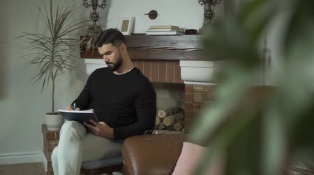 task : Portrait of confident Caucasian bearded man sitting at home or at the office and writing. Successful businessman or psychologist dealing with tasks. Handsome guy thinking on future project