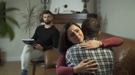 Young attractive Caucasian family hugging, psychologist sitting at the background and smiling. Happy man and woman solving their psychological problems with professional help. Successful therapy Stock Footage