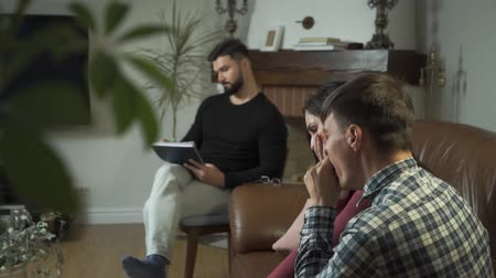 Tired Caucasian family sitting at the foreground and yawning, psychologist taking notes at the background. Young man and woman solving their psychological problems with professional help Stock Footage