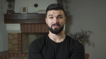 стремление : Close-up portrait of handsome Caucasian man with black hair and beard talking at the camera. Attractive guy sitting at home Стоковые видеозаписи