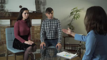 preocupações : Young Caucasian psychologist talking to upset couple in her office. Professional psychoanalist explaining future treatment course to patients. Man and woman listening carefully. Relationship problems