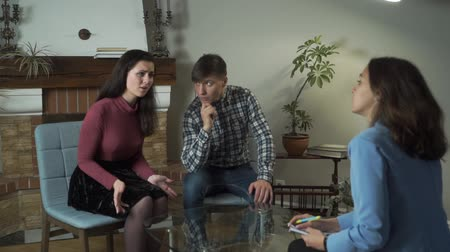 compreensão : Anxious Caucasian wife talking with psychologist about problems she has. Young handsome man sitting next to his spouse and listening carefully. Relationship, problems, devotion, empathy