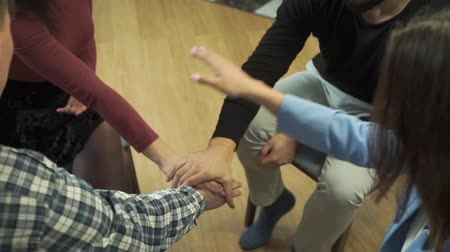 Close-up of four Caucasian hands putted on top of each other. People sitting in circle with friends. Group therapy, psychological treatment, empathy, unity
