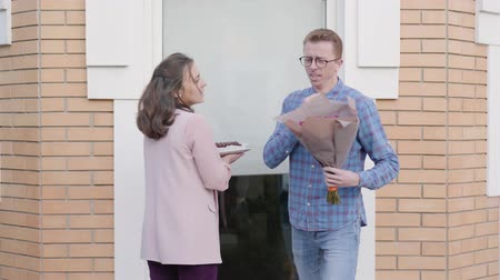 roodharige : Back view of young Caucasian couple coming to the entrance door with a bouquet of red roses and cake. Nervous redhead man in eyeglasses panicking before meeting with his girlfriends parents Stockvideo
