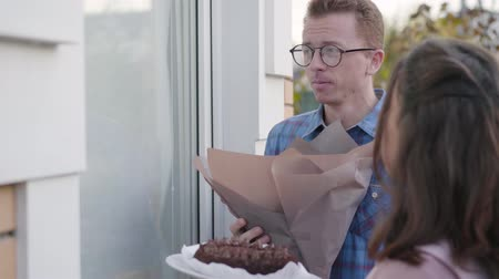 fiancee : Side view of nervous redhead Caucasian man in eyeglasses knocking the door. His fiancee standing next to him with a delicious cake. Meeting with parents, acquaintance, family gathering