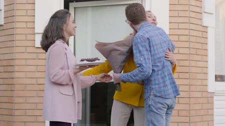 acalmar : Positive Caucasian senior woman in yellow jacket opening the entrace door and welcoming her daughter and her groom. Beautiful girl calming down her fiancee and couple coming into the house