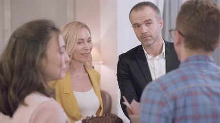 fiancee : Young Caucasian woman introducing her groom to parents. Severe senior man and his positive blond wife acquainting with their daughters fiancee. Meeting with parents, acquaintance, family gathering