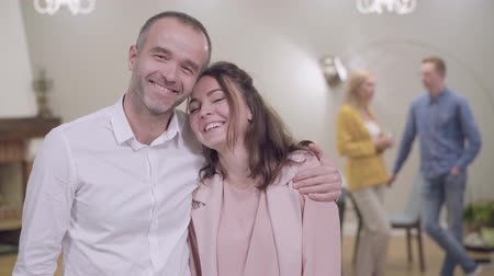 Portrait of happy Caucasian father and daughter looking at the camera and smiling. Mother and son-in-law chatting at the background. Family gathering, meeting with parents Stock Footage