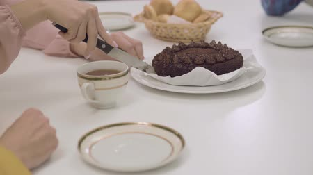 pite : Close-up of a delicious chocolate cake at the table. Female Caucasian hands cutting tasty dessert in four pieces. Family dinner