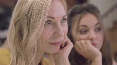 stories : Close-up face of senior blond woman with beautiful grey eyes listening carefully to someones story. Focus changes to young pretty girl sitting next to her mother. Family gathering Stock Footage