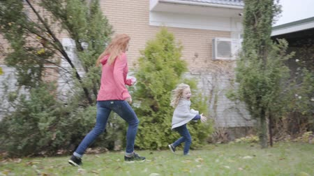 femme rousse : Caucasian mother and daughter running around in the house yard. Cheerful family having fun at weekends. Happy little blond girl with curly hair and redhead adult woman enjoying free time together