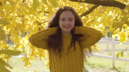 mustár : Portrait of a cute caucasian girl with long curly hair smiling to the camera on the background of yellow leaves. Redhead child in mustard sweater resting in the autumn park
