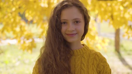 mustár : Pretty caucasian redhead girl with long curly hair standing on the background of yellow leaves and smiling to the camera. Cute child in mustard sweater resting in the autumn park