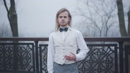 antiquado : Portrait of elegant young blue-eyed boy in stylish white shirt, vest, and bow tie. Confident Caucasian man holding old-fashioned hand clock. Noble guy in love waiting for his sweetheart outdoors