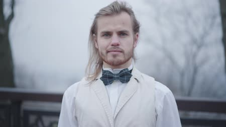 nobreza : Portrait of young confident Caucasian man with long hair and blue eyes dressed in white shirt, vest, and plaid bow tie. Elegant boy looking at camera and smiling. Noble guy in love waiting for his sweetheart outdoors Vídeos