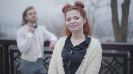 nobreza : Close-up of beautiful Caucasian woman with double buns smiling on the bridge. Old fashioned girl posing in the autumn park as her stylish boyfriend in white vest and bow tie standing at the background.