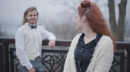 vlinderdas : Beautiful Caucasian woman with double buns looking back at her boyfriend wearing shirt, vest and bow tie, turning to camera and smiling. Retro style couple dating in the autumn park