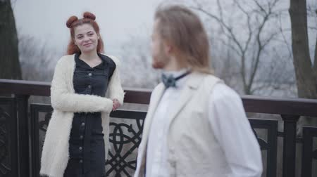 nobreza : Portrait of retro style couple dating in the autumn park. Young Caucasian man in stylish vest and bow tie looking back at his pretty girlfriend, turning to camera and smiling. Focus changes from foreground to back and backwards.