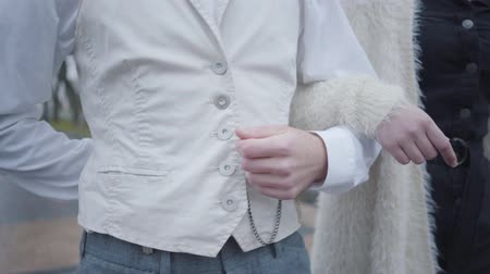 vest : Close-up of male and female Caucasian hands. Boyfriend and girlfriend walking arm-in-arm. Man in white shirt and vest and woman in elegant clothes strolling together outdoors