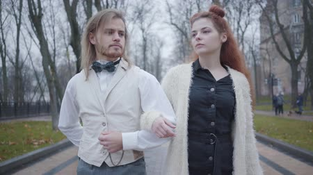 dvojitý : Close-up of young Caucasian couple walking arm-in-arm. Man in white shirt and vest and and plaid bow tie, and woman with double buns strolling together outdoors. Romantic date, happiness Dostupné videozáznamy