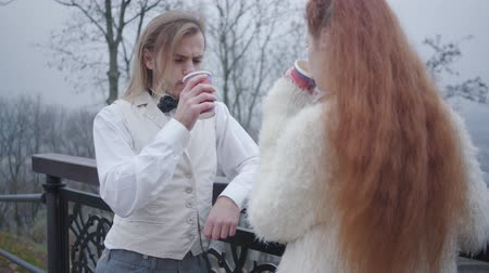 charisma : Back view of redhead Caucasian woman talking to the boy in retro style white shirt and vest, and plaid bow tie. Young couple standing in autumn park and drinking hot tea or coffee. Unusual couple dating outdoors. Stock Footage
