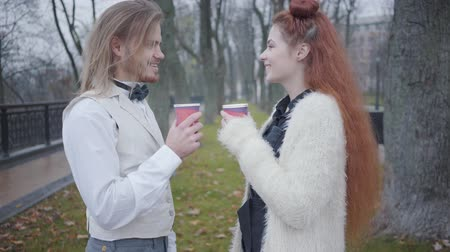dvojitý : Side view of young Caucasian boyfriend and girlfriend standing face to face in autumn park and talking. Redhead woman with double buns fixing plaid bow tie of stylish man. Unusual couple dating outdoors
