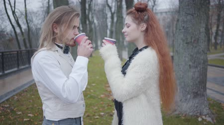 charisma : Side view of young Caucasian couple drinking tea or coffee in autumn park and talking. Boyfriend and girlfriend in retro style clothes dating outdoors