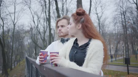 charisma : Side view of charming Caucasian girl with red hair talking to stylish boy with long hair. Young couple dating in autumn park. Unusual boyfriend and girlfriend standing at the bridge with hot tea or coffee.