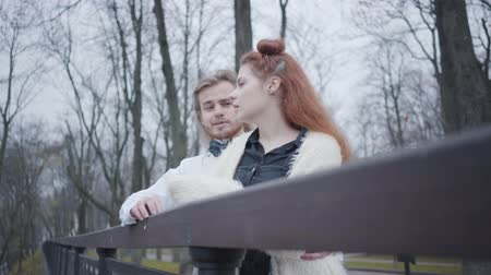 redhair : Bottom shot of charming Caucasian couple standing at the bridge and talking. Stylish boy and girl dating in autumn park. Unusual boyfriend and girlfriend resting outdoors
