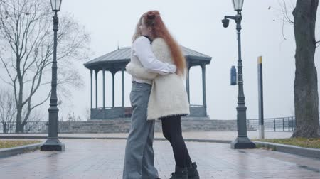 antiquado : Side view of happy young Caucasian couple hugging at the background of summer house. Stylish boyfriend and girlfriend dating in autumn park Stock Footage