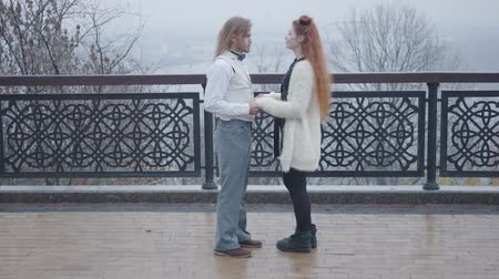 dvojitý : Side view of young Caucasian man taking his girlfriends hands and talking. Happy couple standing face to face in autumn park. Old-fashioned man in white shirt and vest, and redhead woman with double buns resting outdoors. Dostupné videozáznamy