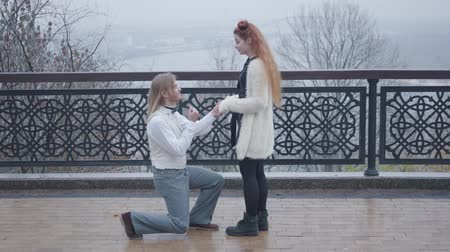 charisma : Side view of stylish boy in elegant retro style clothes bending down on one knee and proposing to his girlfriend. Young Caucasian couple dating at bridge in the autumn park Stock Footage