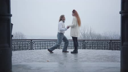 žádat : Long shot of stylish man in retro style shirt and vest bending down on one knee and proposing to his girlfriend. Young Caucasian man giving wedding ring to woman and hugging his future wife