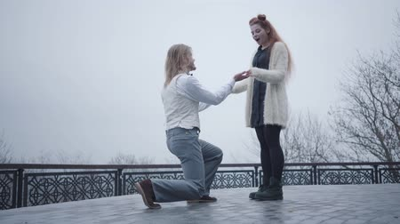 pareja elegante : Side view of stylish boy in white shirt and vest standing on one knee and proposing to his girlfriend. Beautiful Caucasian redhead woman saying yes and taking wedding ring. Young man standing up and hugging his lovely girlfriend Archivo de Video