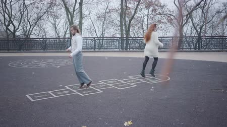 red tie : Joyful millennial couple playing hopscotch outdoors. Adult man in white shirt, vest and plaid bow tie, and woman with red double buns jumping and having fun in autumn park. Funny dating, happiness